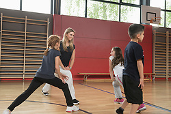 Teacher doing extension exercise with school children in sports hall, Munich, Bavaria, Germany