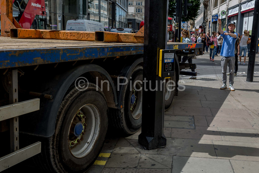 A passer-by directs an articulated lorry as it squeezes past a pedestrian crossing post, making a tight turn across the pavement, on 1st August 2017, in Oxford Street, London, England.
