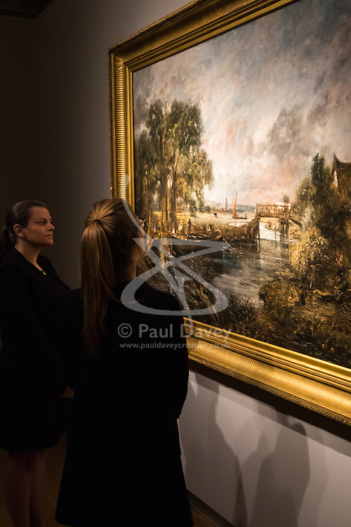 """Christie's, St James, London. Two members of staff admire the brush stroke of one of Britain's most loved painters as Christie's in London announce the sale of a work of genius by John Constable, the full scale six-foot """"sketch"""" for """"View on the Stour near Dedham"""" painted between 1821 and 1822, which is expected to fetch between £18-22 million at auction."""