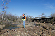 Marco Candia, quality control and safety officer of Kickapoo Empire LLC, checks his phone after an on-site meeting with contractors as Kickapoo Empire LLC and DDM Construction Corporation begin moving dirt in the upper chain of wetlands in the Trinity River near Cedar Crest Blvd. in Dallas, Texas, on January 31, 2013.  (Stan Olszewski/The Dallas Morning News)