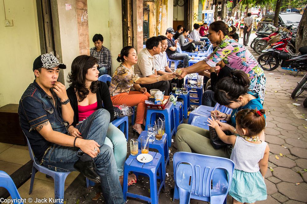 """09 APRIL 2012 - HANOI, VIETNAM:  People eat and drink at street side noodle stands in Hanoi, the capital of Vietnam. Street food has a long tradition in Vietnam. Beer, called """"bia"""" in Vietnamese, is also frequently drunk at street side stands. Hanoi, established in 1010 AD, is one of the oldest permanent cities in Southeast Asia. PHOTO BY JACK KURTZ"""