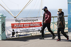 © Licensed to London News Pictures. 04/04/2020. Brighton, UK. People wear face masks as they walk past a sign  saying 'KEEP MOVING and STAY 2 METRES APART'  as they enjoy the sunshine on the seafront at Brighton, West Sussex. As death rates continue to rise the public have been told they can only leave their homes when it is absolutely essential, in an attempt to fight the spread of coronavirus COVID-19 disease. Photo credit: Peter Macdiarmid/LNP