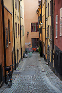 Vertical shot of an alley in Old Town with colorful houses, parked bicycles and graffiti.