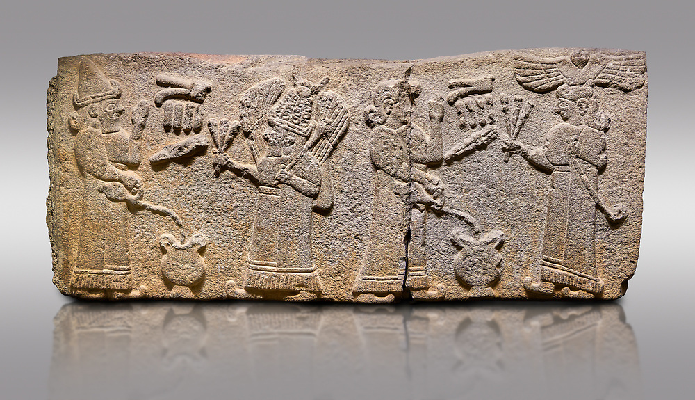 Aslantepe Monumental Hittite relief sculpted orthostat stone panel.  Limestone, Aslantepe, Malatya, 1200-700 B.C. <br /> <br /> Scene of the king's offering drink and sacrifice to the gods. The king offers to the winged god of the moon who stands across and holds a lightning bundle in his hand. Behind the king is the queen, who also offers to goddess of the sun holding a sceptre in his hand. King's left hand is in a position to worship. <br /> <br /> Against a gray background. .<br /> <br /> If you prefer to buy from our ALAMY STOCK LIBRARY page at https://www.alamy.com/portfolio/paul-williams-funkystock/hittite-art-antiquities.html . Type - Aslantepe - in LOWER SEARCH WITHIN GALLERY box. Refine search by adding background colour, place, museum etc.<br /> <br /> Visit our HITTITE PHOTO COLLECTIONS for more photos to download or buy as wall art prints https://funkystock.photoshelter.com/gallery-collection/The-Hittites-Art-Artefacts-Antiquities-Historic-Sites-Pictures-Images-of/C0000NUBSMhSc3Oo