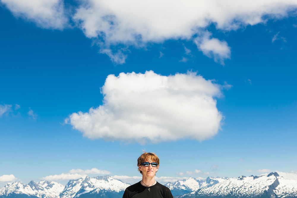Ian Derrington stands under white fluffy clouds on the summit of Damnation Peak, North Cascades National Park, Washington.