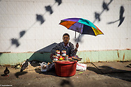 A birds seeds seller is waiting for custumers in a street of Yangon. Feeding birds is one of the practices used by Buddhist worshippers in Myanmar to gain merits and purify their own karma. <br /> Photo by Lorenz Berna