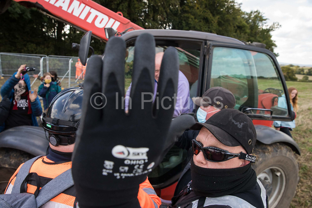 A National Eviction Team bailiff obstructs the photographer's camera as a farmer in a telehandler positioned on land not compulsorily purchased by HS2 Ltd asks for clarification as to why a fence is being erected across his field during the eviction of anti-HS2 activists from a wildlife protection camp in ancient woodland at Jones' Hill Wood alongside the field on 1 October 2020 in Aylesbury Vale, United Kingdom. Around 40 environmental activists and local residents, some of whom living in makeshift tree houses, were present during the evictions at Jones' Hill Wood which had served as one of several protest camps set up along the route of the £106bn HS2 high-speed rail link in order to resist the controversial infrastructure project.