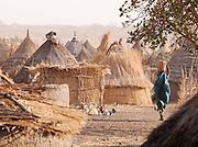 Girl of the Nuba tribe carrying water on her head through the village of Nyaro, Kordofan region, Sudan