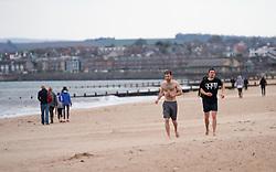 Portobello, Edinburgh, Scotland, UK. 5 April, 2020.  Images of Portobello promenade on the second Sunday of the coronavirus lockdown in the UK. Men jogging on the beach.