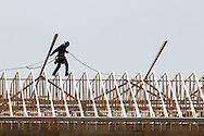 Wawayanda, New York - A man walks across the roof of a three-story building under construction on March 3, 2016.  The structure is being built by Nowak Properties Inc., and will be a 108-room Sleep Inn hotel.