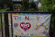 """As Prime Minister Boris Johnson returns to Downing Street after being admitted to hospital suffering from Coronavirus, and confirming that the pandemic lockdown in the UK will continue, telling the country """"we are now beginning to turn the tide"""" on the disease. A further 360 people died with the virus in hospitals today, taking the total number of deaths to 21,092, and a homemade banner has been stitched and hangs on the gates leading to a group of homes on Herne Hill in south London during the lockdown, on 27th April 2020, in London, England."""