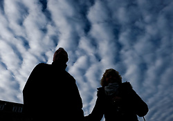 © Licensed to London News Pictures. <br /> 10/01/2017. <br /> Saltburn by the Sea, UK.  <br /> <br /> A couple stand looking out to sea as Altocumulus Undulatus cloud formations form above them over Saltburn by the Sea.<br /> <br /> The wave like pattern is caused by the way the winds vary with altitude and blow at different speeds above and below the cloud layer.<br /> <br /> <br /> Photo credit: Ian Forsyth/LNP