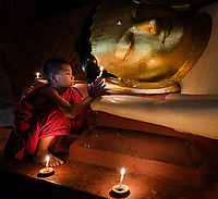 BAGAN, MYANMAR - CIRCA DECEMBER 2017: Young monk lighting candles in a temple in Bagan