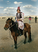 A young teenage girl come to watch the competition, wearing traditional Kazakh outfit.<br /> <br /> Eagle Hunting festival in Western Mongolia, in the province of Bayan Olgii. Mongolian and Kazak eagle hunters come to compete for 2 days at this yearly gathering. Mongolia