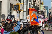 """New York, NY - 11 November 2019. New York City's Veterans Day Parade, today marking the 100th anniversary of the armistice ending the fighting of the first World War, was attended by a number of people protesting President Trump, who spoke at the opening ceremony, and a smaller number of pro-Trump supporters. Sihns here include """"Remove Trump"""" (with an image of someone removing chewing gum from the sole of a shoe), and """"Thanks you veterans for our freedom."""""""