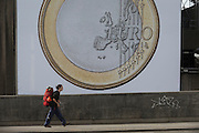A backpacker walks past a giant Euro coin, an artwork by Danish artists Superflex, hanging from the hayward Gallery on Waterloo Bridge, on 3rd February 2017, London, England. For the third Waterloo Billboard Commission, the work is a euro coin with its value conspicuously absent – made by the group in 2012, in response to the Greek financial crisis – has gained new resonance since the UK's decision to leave the EU. The billboard is the third in a series of large-scale commissions by international artists, occupying the prominent billboard site next to Hayward Gallery.