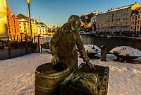 Statue of a fisherwomen sorting through a days catch of fish, Apotekertorget, Alesund, Norway. The town is famous for its art nouveau (Jugendstil) architecture. The  town was rebuilt after a fire in 1904. Alesund is in the heart of Fjord Country, at the entrance to Geirangerfjord on Norway's west coast.