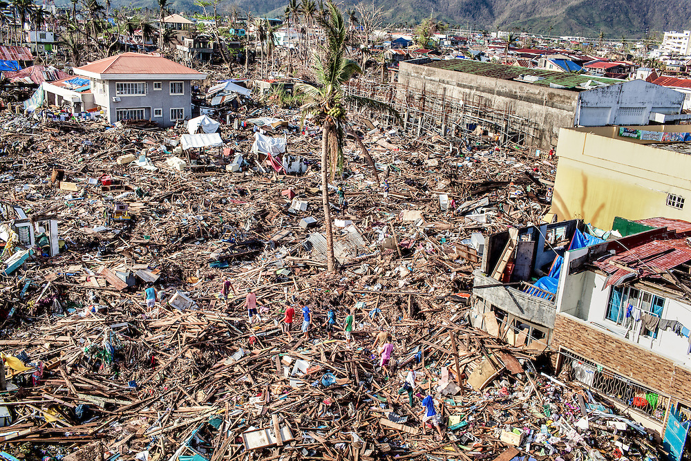 Residents of Tacloban City walk on top of debris from broken homes and items destroyed by Typhoon Haiyan.