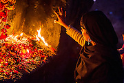 """29th January 2015, New Delhi, India. A woman sticks a coin to a wall as an offering and ask for wishes to be granted by Djinns in the ruins of Feroz Shah Kotla in New Delhi, India on the 29th January 2015<br /> <br /> PHOTOGRAPH BY AND COPYRIGHT OF SIMON DE TREY-WHITE a photographer in delhi. + 91 98103 99809. Email:simon@simondetreywhite.com<br /> <br /> People have been coming to Firoz Shah Kotla to leave written notes and offerings for Djinns in the hopes of getting wishes granted since the late 1970's. Jinn, jann or djinn are supernatural creatures in Islamic mythology as well as pre-Islamic Arabian mythology. They are mentioned frequently in the Quran  and other Islamic texts and inhabit an unseen world called Djinnestan. In Islamic theology jinn are said to be creatures with free will, made from smokeless fire by Allah as humans were made of clay, among other things. According to the Quran, jinn have free will, and Iblīs abused this freedom in front of Allah by refusing to bow to Adam when Allah ordered angels and jinn to do so. For disobeying Allah, Iblīs was expelled from Paradise and called """"Shayṭān"""" (Satan).They are usually invisible to humans, but humans do appear clearly to jinn, as they can possess them. Like humans, jinn will also be judged on the Day of Judgment and will be sent to Paradise or Hell according to their deeds. Feroz Shah Tughlaq (r. 1351–88), the Sultan of Delhi, established the fortified city of Ferozabad in 1354, as the new capital of the Delhi Sultanate, and included in it the site of the present Feroz Shah Kotla. Kotla literally means fortress or citadel."""