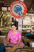 25 JUNE 2011 - CHIANG MAI, THAILAND: A worker at an umbrella shop in a craft village near Chiang Mai, Thailand. Umbrellas from the Chiang Mai are prized throughout Thailand for the quality of workmanship. They were once used almost exclusively as sun parasols by Buddhist monks and royalty but now are used by hotels, restaurants and collectors.   PHOTO BY JACK KURTZ