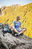 A woman hiker sitting on the edge of a rocky cliff, Little Si Trail, Washington, USA.