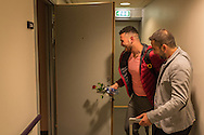 Nader (grey jacket) leads Omar into their apartment in Bergen, Norway. Nader has filled it with candles in a heart shape, with the letters O and N in the middle.