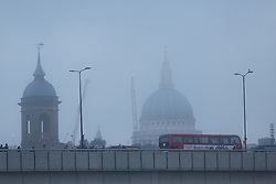 © Licensed to London News Pictures. 22/12/2016. LONDON, UK.  Commuters and a bus pass in front of St Paul's Cathedral during fog this morning. After a cold and foggy start to the day, London is now seeing bright and sunny weather today. Photo credit: Vickie Flores/LNP