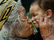 """Bertha Norton age 101, gives her great great grandson Joshua Ramirez 16 months, a pinch and a kiss. Bertha is from Miadu and Wintun tribes.  PIcture taken the California State Indian Museum while celebrating """"Gathering of Honored Elders""""."""