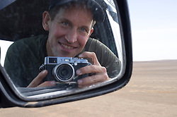 Sell-portrait in car mirror on desert road near Erg Chebbi, Saharan Desert, Morocco
