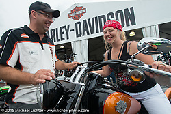 April Flatt of Deluth, MN checks out a new Harley with the help of HD's Charley Lambof at the Harley display during the 75th Annual Sturgis Black Hills Motorcycle Rally.  SD, USA.  August 4, 2015.  Photography ©2015 Michael Lichter.