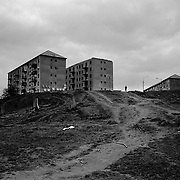 A housing estate containing inhabited and  unfinished communist style housing blocks which stand in the heart of the housing estate of the small Romanian town of Copsa Mica  Transylvania, Romania. Copsa Mica was once described as the most polluted town in Europe. May 8, 2008 Photo Tim Clayton...Copsa Mica, a small industrial town deep in Transylvania, Romania, was described during the 1990s as the most polluted town in Europe with lead levels reaching were more than 1000 times the allowable International limits and life expectancy nine years shorter than the National average...The pollution was caused entirely by two factories, Carbosin produced black for dies and tires and closed in 1993 while Sometra, a nonferrous smelter is still operational today...The pollution was so bad sheep were black, covered in soot and health officials advised against eating livestock or vegetables and drinking the water or milk...The Communist rule of Nicolae Ceausescu is blamed for the widespread environmental degradation that left industrial parts of Romania in ecological disaster. Industry was situated in a way to concentrate pollution in small areas leaving the rest of the country relatively free of pollution.Copsa Mica in particular was left an environmental disaster...The pollution caused a direct affect on human health with widespread Lung disease, Impotency, the highest infant mortality rate in Europe, Lead poisoning andbehavioral problems...Fifteen years on since the closure of Carbosin in 1993, the factory skeleton remains as part of the towns bleak landscape, Unfinished communist style housing blocks still stand in the heart of the towns housing estate. The town's inhabitants arestill trying to recover from the long lasting effects of pollution...Recent survey's found the soil contained so much lead that it was 92 times above the permitted level; the vegetation had a lead content 22 times above the permitted level. While toxins have penetrated at least