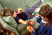 Sisters playing doctor and taking blood pressure on sofa age 3 and 5.  WesternSprings  Illinois USA