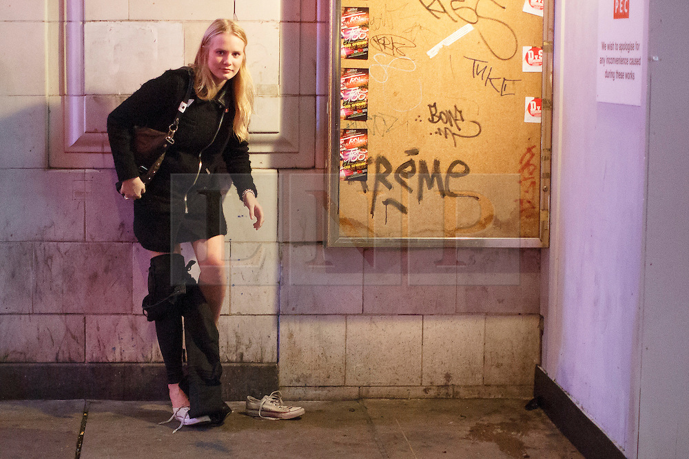 """© licensed to London News Pictures. London, UK 14/12/2013. A """"Mad Friday"""" reveller changing her clothes in the street in Soho, London whilst enjoying the last Friday night out before Christmas, which is also the busiest night of the year for emergency services. Photo credit: Tolga Akmen/LNP"""