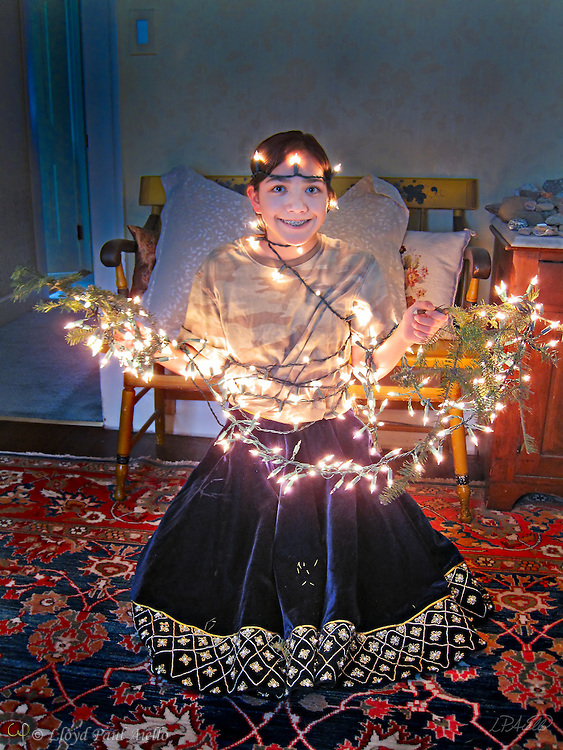 Ashlyn (age 12) decks herself with the lights and boughs of the just dismantled Christmas tree