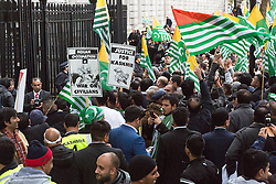 """© Licensed to London News Pictures. 26/10/2014. London, UK. Protesters outside Downing Street who have taken part in the """"Kashmir Million March"""" rally in central London on 26th October 2014 to raise awareness of the """"forgotten millions"""" they say are suffering under the Indian occupation in the region of Kashmir. The demonstration marched from Trafalgar Square to Downing Street in Whitehall, London, where a petition was delivered to David Cameron, the British Prime Minister's residence asking Britain to push India into resolving the Kashmir situation with Pakistan. Photo credit : Vickie Flores/LNP"""