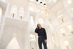 A gallery assistant looks at dresses during the preview into the 'Christian Dior: Designer of Dreams' at the Victoria and Albert Museum, London. Picture dated: Wednesday January 30, 2019. Photo credit should read: Isabel Infantes / EMPICS Entertainment.