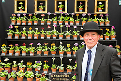 © Licensed to London News Pictures. 19/05/2014. London, England. A flower grower poses in front of his stand.  Press Day at the RHS Chelsea Flower Show. On Tuesday, 20 May 2014 the flower show will open its doors to the public.  Photo credit: Bettina Strenske/LNP