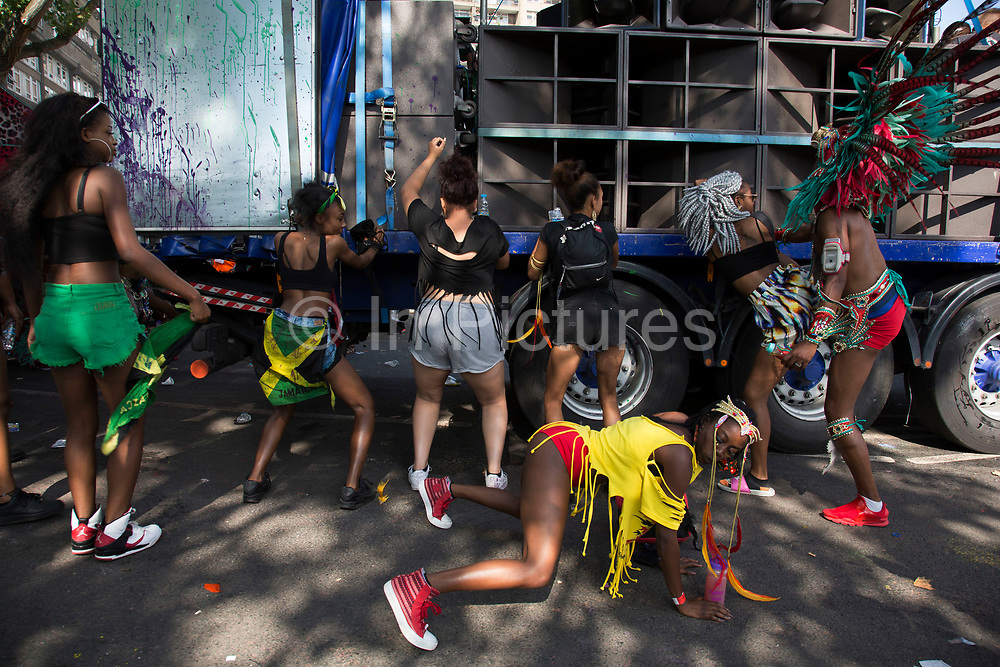 Group of young women daggering against a sound system truck on Monday 28th August 2016 at the 50th Notting Hill Carnival in West London. This modern dance came from dancehall music around 2006. A celebration of West Indian / Caribbean culture and Europes largest street party, festival and parade. Revellers come in their hundreds of thousands to have fun, dance, drink and let go in the brilliant atmosphere. It is led by members of the West Indian / Caribbean community, particularly the Trinidadian and Tobagonian British population, many of whom have lived in the area since the 1950s. The carnival has attracted up to 2 million people in the past and centres around a parade of floats, dancers and sound systems.