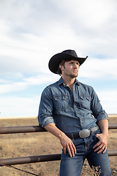 Hot All American cowboy by a rustic fence on a ranch