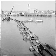 """9904-B02-4. """"Dredge pipe & pontoons holding up electric cable at Crown Mills, March 26, 1957"""" caption published in the Oregonian March 26, 1957 pg. 15 """"Tug Plucks Power Cables to aid River Dredging."""" (Cable went from Crown Mills to the Permanente Cement plant. 120mm negatives. View looking west, showing the east bank of the Willamette River.)"""