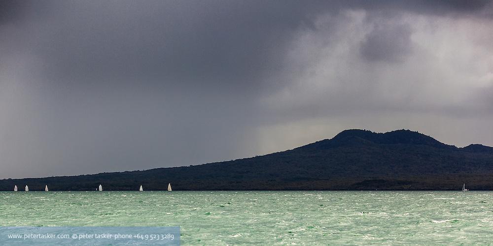 Rainy day with distant yachts sailing along the coast of Rangitoto Island. Waitemata Harbour, Auckland, New Zealand.