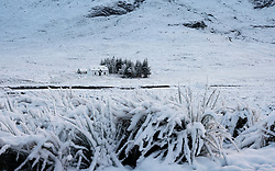 Glen Coe, Scotland, UK. 3 December 2020. A cold front has brought the first snowfall to the Scottish Highlands. Rannoch Moor and Glen Coe are covered in several inches of snow. Bright sunshine throughout the day created beautiful winter landscapes.  Pictured; Solitary cottage in the snow.  Iain Masterton/Alamy Live News