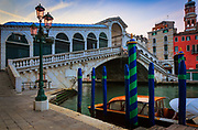 "The sun is rising above the Rialto Bridge on Venice's Grand Canal, Italy<br /> .....<br /> Venice is a city in northeastern Italy sited on a group of 118 small islands separated by canals and linked by bridges. It is located in the marshy Venetian Lagoon which stretches along the shoreline, between the mouths of the Po and the Piave Rivers. Venice is renowned for the beauty of its setting, its architecture and its artworks. The city in its entirety is listed as a World Heritage Site, along with its lagoon. Venice is the capital of the Veneto region. In 2009, there were 270,098 people residing in Venice's comune. Although there are no historical records that deal directly with the founding of Venice, tradition and the available evidence have led several historians to agree that the original population of Venice consisted of refugees from Roman cities near Venice such as Padua, Aquileia, Treviso, Altino and Concordia (modern Portogruaro) and from the undefended countryside, who were fleeing successive waves of Germanic and Hun invasions. Some late Roman sources reveal the existence of fishermen on the islands in the original marshy lagoons. They were referred to as incolae lacunae (""lagoon dwellers""). The traditional founding is identified with the dedication of the first church, that of San Giacomo at the islet of Rialto (Rivoalto, ""High Shore""), which is said to have been at the stroke of noon on 25 March 421."