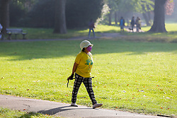 © Licensed to London News Pictures. 07/09/2021. London, UK. A walker wearing a sun hat and a face covering   enjoys a warm morning in Chestnuts Park, north London as the mini heatwave continues in London. According to the Met office, temperatures over 28 degree Celsius are forecast today in London and the South East of England. Photo credit: Dinendra Haria/LNP