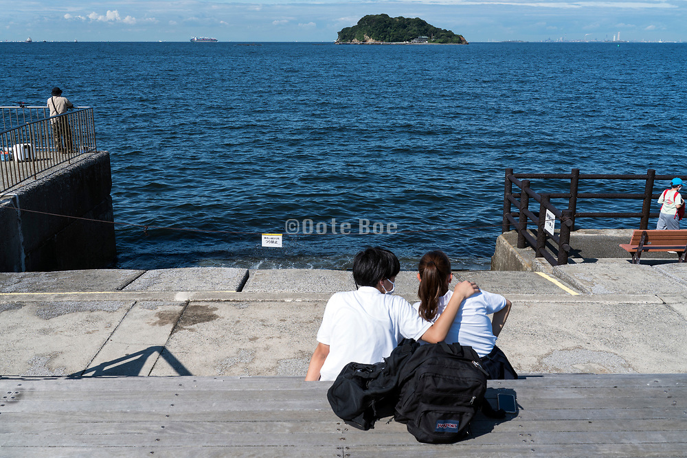 young couple looking out over Tokyo Bay and Sarushima Island at Umikaze park Yokosuka