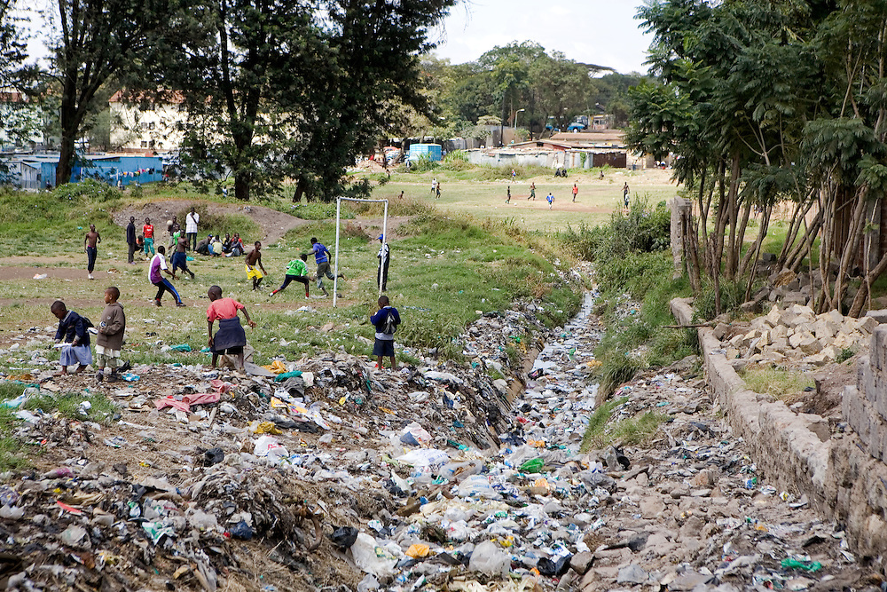 The community football pitch in the Pumwani slum is adjacent to one of the many open sewers, children often scavenge in the sewers to find items they can play with or recycle.