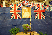 """""""New Covent Garden Wholesale Flower Market"""" (Photograph must be captioned like this - I had to sign a contract!!)<br /><br />A faded picture of the Queen sits amongst British flags and bunting adorn Pratley's market flower shop at New Covent Garden Wholesale Flower Market<br /><br />The main selling days for local British fresh flowers are on Monday and Thursday mornings. The main sellers are Pratleys<br /><br />British local flowers, grown nearby, count for around 10% of the UK market, traveling less than a tenth of their foreign counterparts which are often flown in from abroad. Nearly 90% of the flowers sold in the UK are actually imported, and many travel over 3000 miles. Local flower farms help biodiversity, providing food and habitat to a huge variety of wildlife, insects including butterflies, bugs, and bees. Often local flower farmers prefer to grow organic rather than using pesticides. British flowers bloom all the year around, even in the depths of winter, and there are local flower farms throughout the country.<br /><br />Many people like the idea of the just picked from the garden look, and come to flower farms throughout Britain to pick their own for weddings, parties and garden fetes. Others come for the joy of a day out in the countryside with their family. Often a bride and her family will come to pick the flowers for her own wedding, some even plant the seeds earlier in the year."""