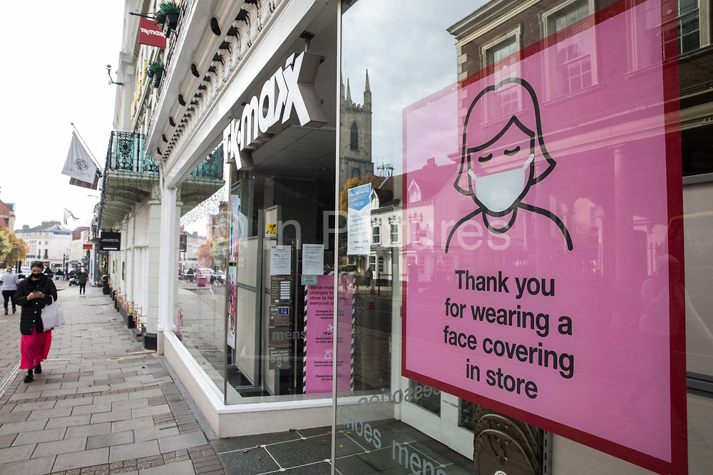 """A woman walks past a closed branch of American department store chain TK Maxx on the second day of England's second coronavirus lockdown on 6 November 2020 in Windsor, United Kingdom. Only retailers selling """"essential"""" goods and services are permitted to remain open to the public during the second lockdown provided that they follow coronavirus guidelines and make their premises COVID-19 secure."""