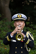 Bugler, Lieutenant Hiromi Watanabe plays the Last Post during the Remembrance Sunday ceremony at the Hodogaya, Commonwealth War Graves Cemetery in Hodogaya, Yokohama, Kanagawa, Japan. Sunday November 11th 2018. The Hodagaya Cemetery holds the remains of more than 1500 servicemen and women, from the Commonwealth but also from Holland and the United States, who died as prisoners of war or during the Allied occupation of Japan. Each year officials from the British and Commonwealth embassies, the British Legion and the British Chamber of Commerce honour the dead at a ceremony in this beautiful cemetery. The year 2018 marks the centenary of the end of the First World War in 1918.
