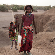 Rabia and Hassan climb up  from the dried up river bed and head off to rejoin with their mother and their herd of goats. It's dry season in Afar and water is hard to come by. A hole has been dug into the river bed to be able to find something to drink. Both animals and humans suffer in the dry season and travel long distances to find water and grassing.  Rabia and her family are pastoralists and have come to water their goats. Action for Integrated Sustainable Development Association (AISDA) work in the AFAR region of Eastern Ethiopia, based in Delafagi. The Afars practise an old tradition of Female Genital Mutilation where the baby girls has her clitoris and labia cut away and her vagina sewn up. The day before her wedding day the girl is un-stiched ready for marriage. Its a brutal and barbaric tradition which AISDA is challenging with great effect, now more than a hundred girls in Dowe district have been saved from the knife and AISDA is now rolling out the scheme in Delafagi. Delafagi is where the oldest ever human remains have been found, the found is thought to be 4.5 mill years old.
